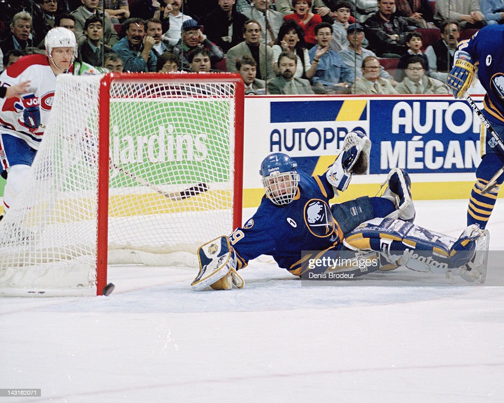 Dominik Hasek of the Buffalo Sabres watches as the puck rolls past the post and wide of the net during a game against the Montreal Canadiens Circa...