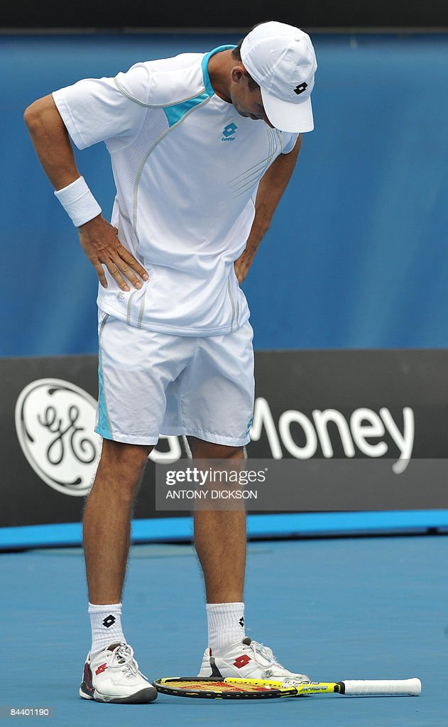 Dominik Hrbaty of Slovakia looks down towards his racquet during his men's singles match against David Ferrer of Spain at the Australian Open tennis tournament in Melbourne on January 21, 2009. Ferrer won 6-2. 6-2. 6-1. .AFP PHOTO/Antony DICKSON