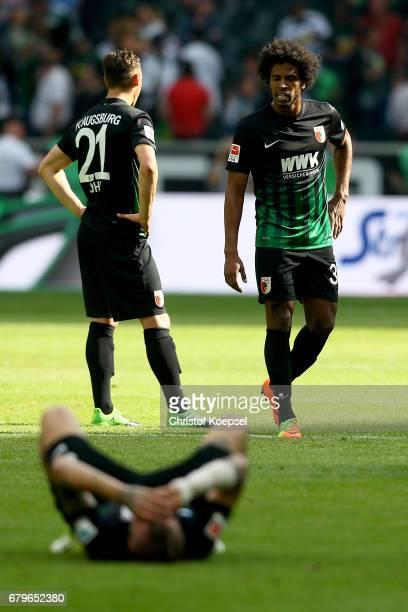 Dominik Kohr Konstantinos Stafylidis and Caiuby of Augsburg look dejected after the Bundesliga match between Borussia Moenchengladbach and FC...