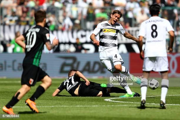 Dominik Kohr of Augsburg fouls Jannik Vestergaard of Moenchengladbach during the Bundesliga match between Borussia Moenchengladbach and FC Augsburg...