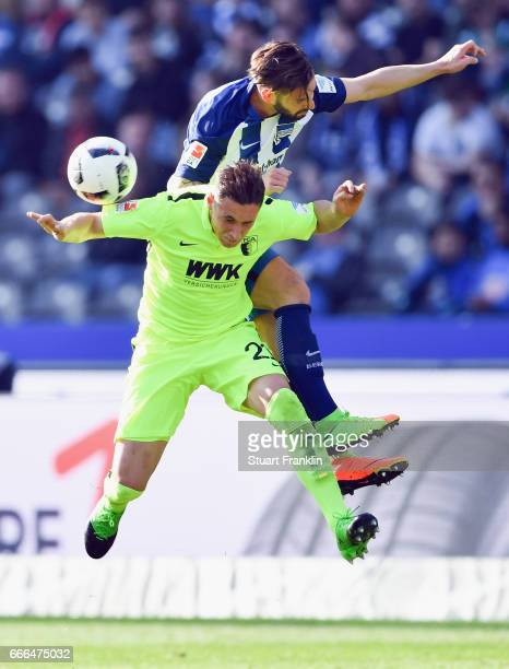 Dominik Kohr of Augsburg jumps for a header with Marvin Plattenhardt of Berlin during the Bundesliga match between Hertha BSC and FC Augsburg at...