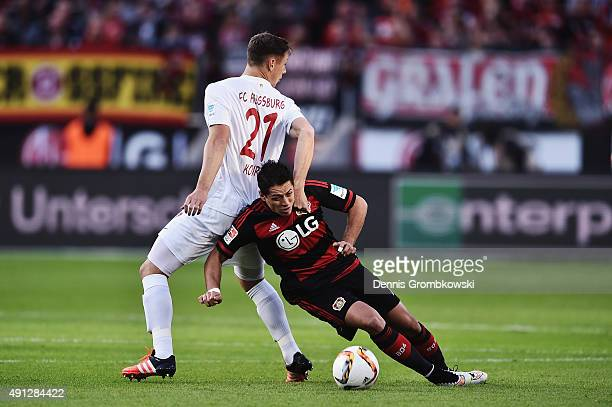Dominik Kohr of FC Augsburg and Chicharito of Bayer Leverkusen battle for the ball during the Bundesliga match between Bayer Leverkusen and FC...