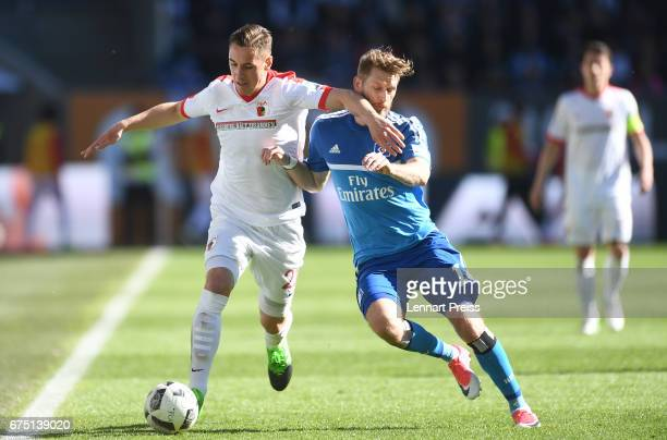 Dominik Kohr of FC Augsburg challenges Aaron Hunt of Hamburger SV during the Bundesliga match between FC Augsburg and Hamburger SV at WWK Arena on...