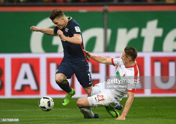 Dominik Kohr of FC Augsburg challenges Marcel Sabitzer of RB Leipzig during the Bundesliga match between FC Augsburg and RB Leipzig at WWK Arena on...