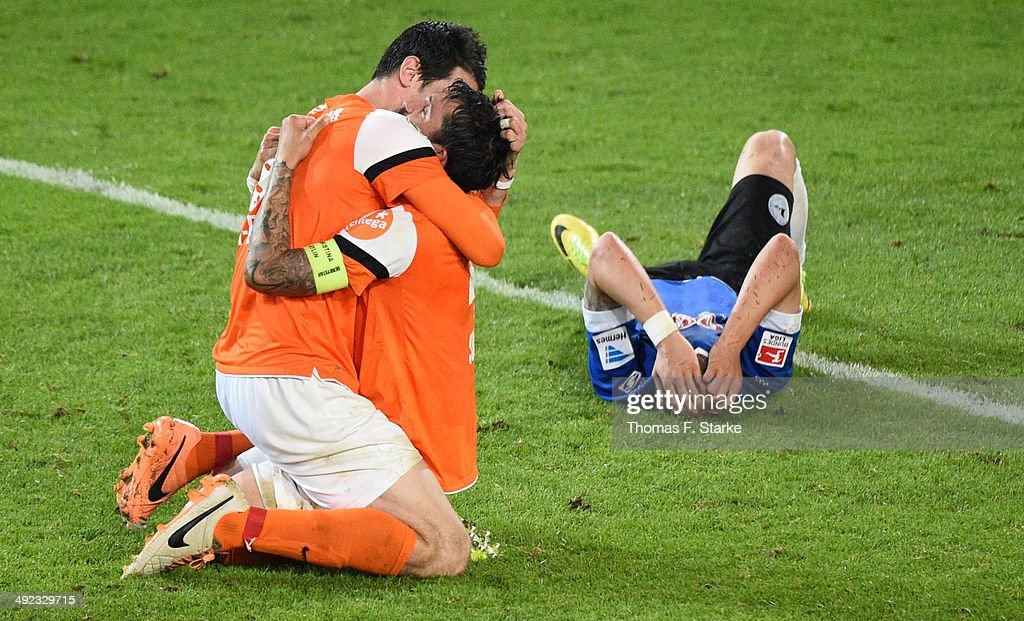 Dominik Stroh - Engel (L) and Benjamin Gorka (C) of Darmstadt celebrate while a Bielefeld player looks dejected after the Second Bundesliga Playoff Second Leg match between Arminia Bielefeld and Darmstadt 98 at Schueco Arena on May 19, 2014 in Bielefeld, Germany.