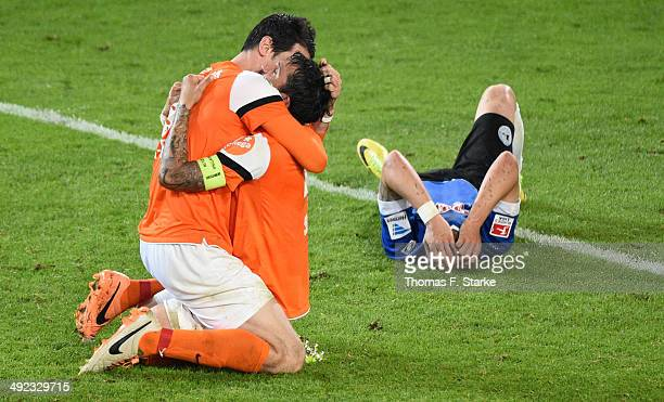 Dominik Stroh Engel and Benjamin Gorka of Darmstadt celebrate while a Bielefeld player looks dejected after the Second Bundesliga Playoff Second Leg...