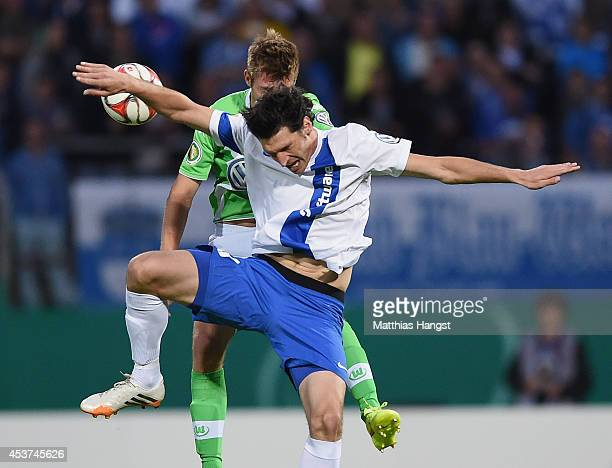 Dominik StrohEngel of Darmstadt jumps for a header with Robin Knoche of Wolfsburg during the DFB Cup first round match between SV Darmstadt 98 and...