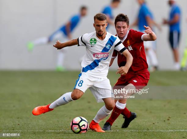 Dominik Szabo of MTK Budapest II competes for the ball with Liam Coyle of FC Liverpool U23 during the Preseason Friendly match between MTK Budapest...