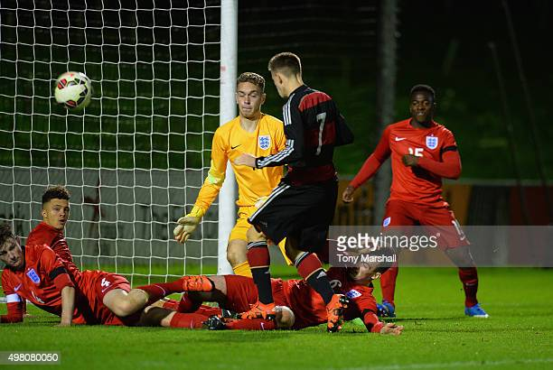 Dominik Wanner of Germany kicks the ball past Ryan Sandford of England to score a goal during the U17s International Friendly match between England...