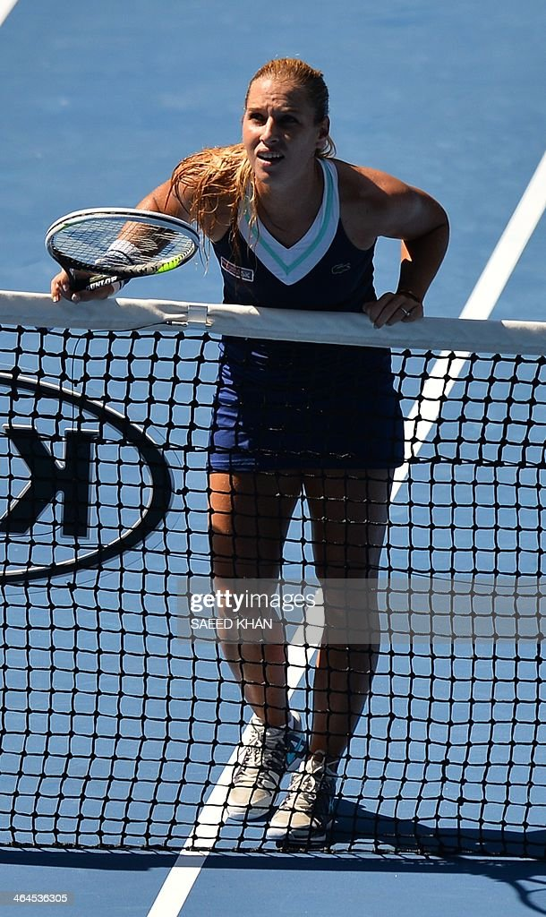 Dominika Cibulkova of Slovakia leans on the net while playing against Agnieszka Radwanska of Poland during their women's singles semi-final match on day 11 of the 2014 Australian Open tennis tournament in Melbourne on January 23, 2014. AFP PHOTO / SAEED KHAN USE