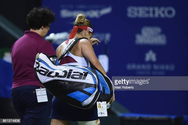 Dominika Cibulkova of Slovakia leaves the court after retiring injured in her quarter final match against Caroline Wozniacki of Denmark during day...