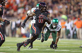 Dominique Brown of the Louisville Cardinals runs with the ball during the game against the Miami Huricanesat Papa John's Cardinal Stadium on...