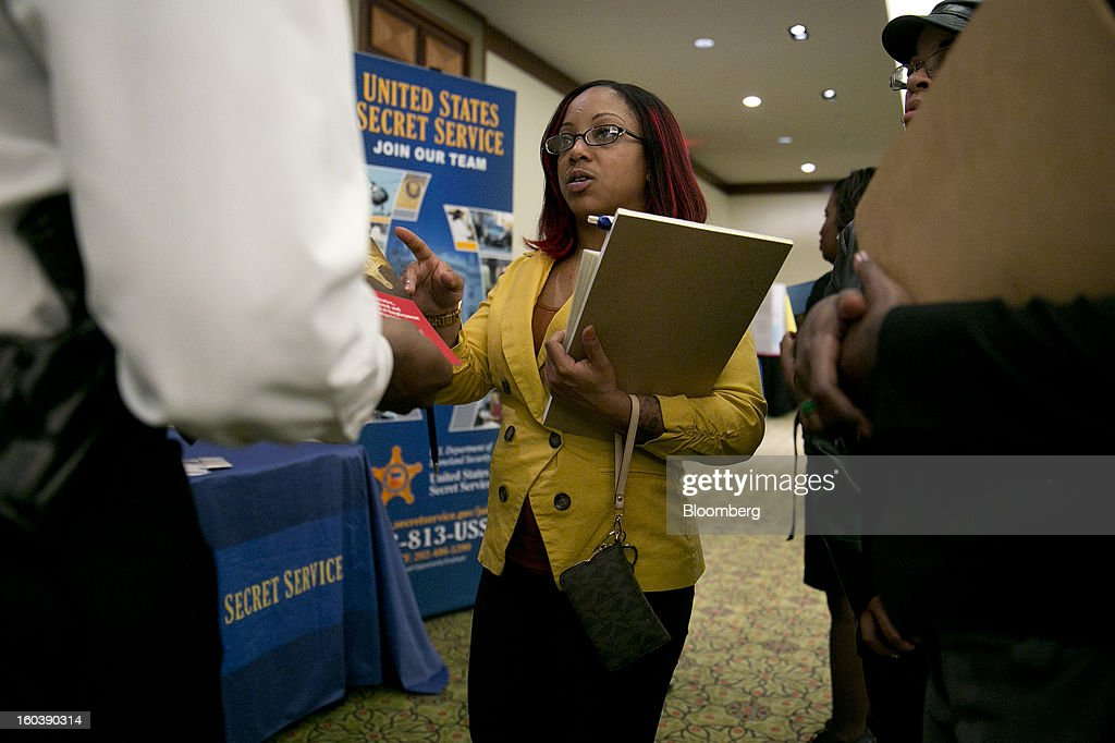 Dominique Butler talks to a job recruiter at a National Career Fairs job fair in Arlington, Virginia, U.S., on Wednesday, Jan. 30, 2013. The U.S. Labor Department is scheduled to release initial jobless claims data on Jan. 31. Photographer: Andrew Harrer/Bloomberg via Getty Images