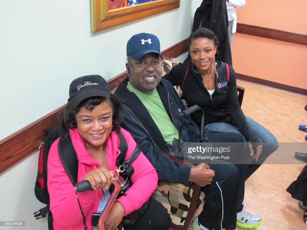 Dominique Dawes, right, greets patients Angela and Steve Truly, left, at the Howard University diabetes treatment center.
