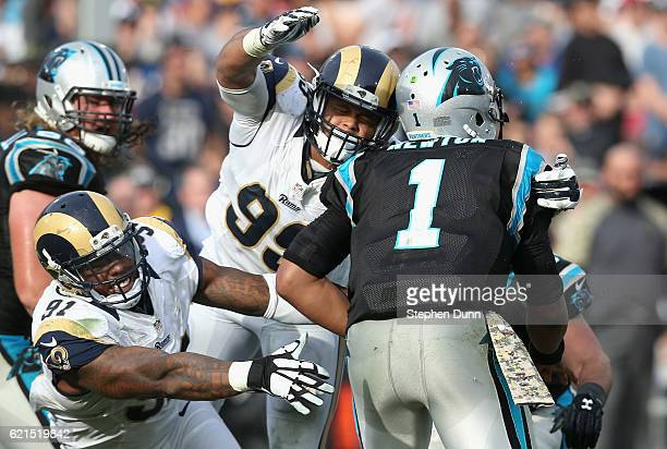 Dominique Easley and Aaron Donald of the Los Angeles Rams reaches for quarterback Cam Newton of the Carolina Panthers during the third quarter of the...