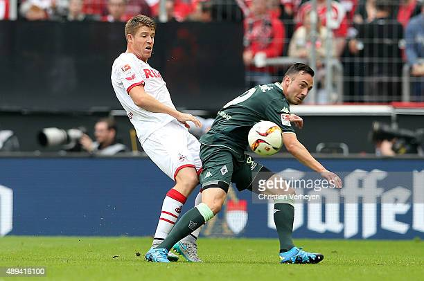 Dominique Heintz of 1 FC Koeln and Josip Drmic of Borussia Moenchengladbach battle for the ball during the Bundesliga match between 1 FC Koeln and...