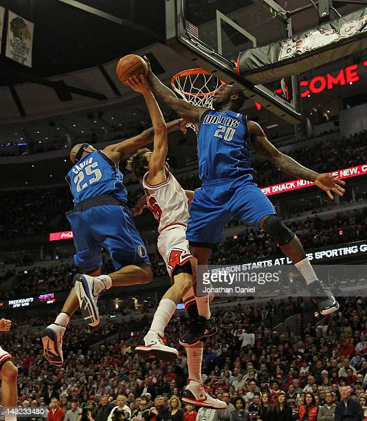 Dominique Jones of the Dallas Mavericks blocks a shot by Kyle Korver of the Chicago Bulls as Vince Carter also defends at the United Center on April...