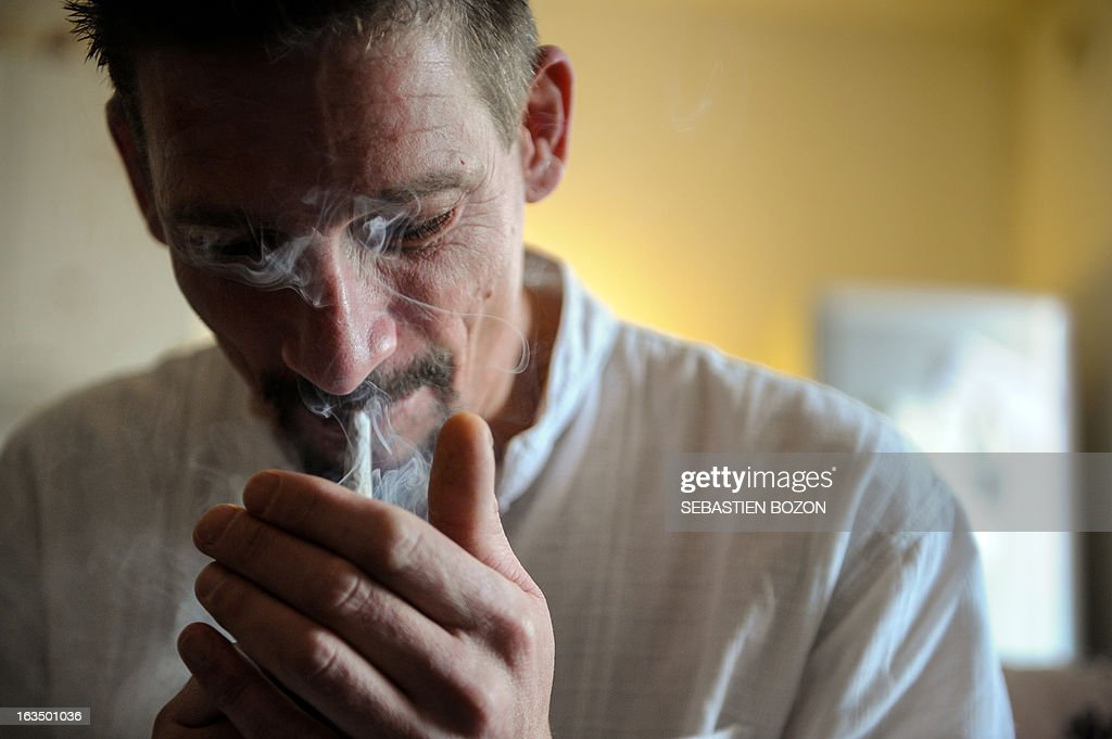 Dominique Loumachi, suffering from Dermatomyositis (Myopathy), lights a cigarette that looks like a cannabis cigarette - in order not to be charged for promoting consumption of narcotic substances - while posing on February 28, 2013 in Belfort, easten France. Domique Loumachi claims the right to use cannabis in therapeutic use. He is currently prosecuted for possession and drug use. A Belfort court will decide on March 13, 2013, if the patient can carry on without been charged.