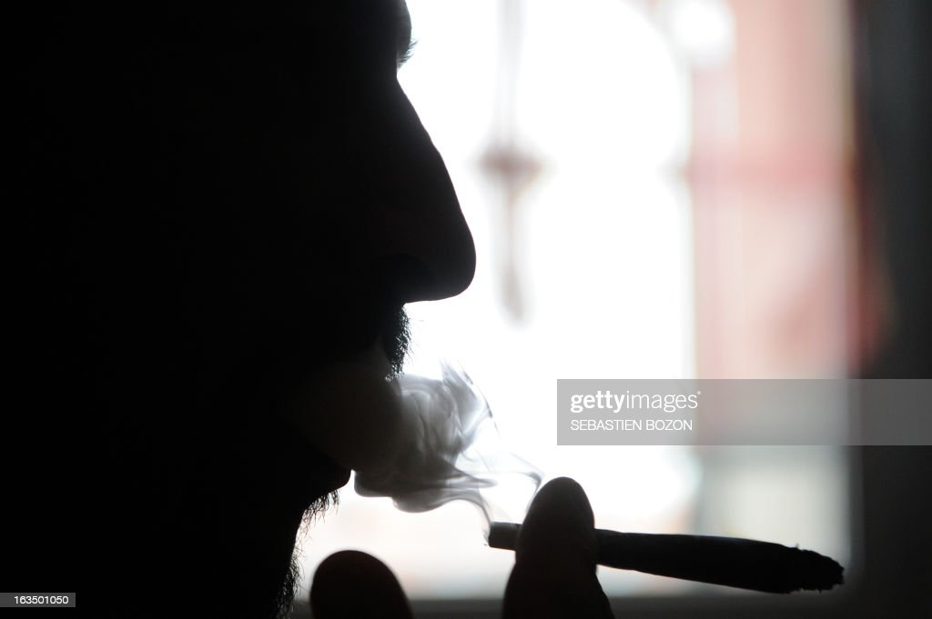 Dominique Loumachi, suffering from Dermatomyositis (Myopathy), smokes a cigarette that looks like a cannabis cigarette - in order not to be charged for promoting consumption of narcotic substances - while posing on February 28, 2013 in Belfort, easten France. Domique Loumachi claims the right to use cannabis in therapeutic use. He is currently prosecuted for possession and drug use. A Belfort court will decide on March 13, 2013, if the patient can carry on without been charged. AFP PHOTO / SEBASTIEN BOZON