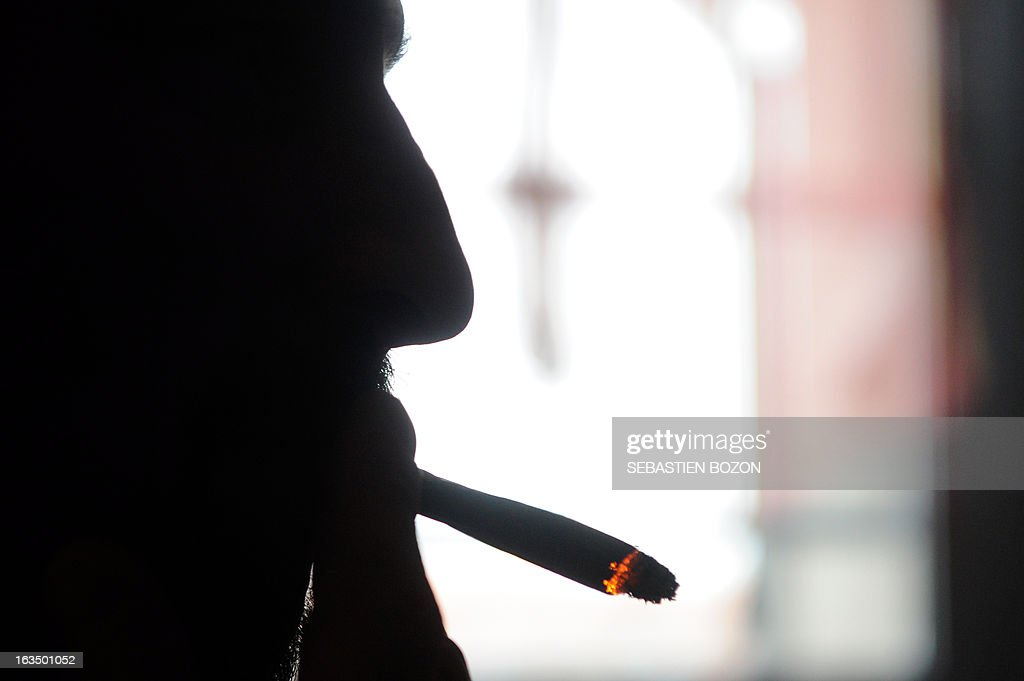 Dominique Loumachi, suffering from Dermatomyositis (Myopathy), smokes a cigarette that looks like a cannabis cigarette - in order not to be charged for promoting consumption of narcotic substances - while posing on February 28, 2013 in Belfort, easten France. Domique Loumachi claims the right to use cannabis in therapeutic use. He is currently prosecuted for possession and drug use. A Belfort court will decide on March 13, 2013, if the patient can carry on without been charged.