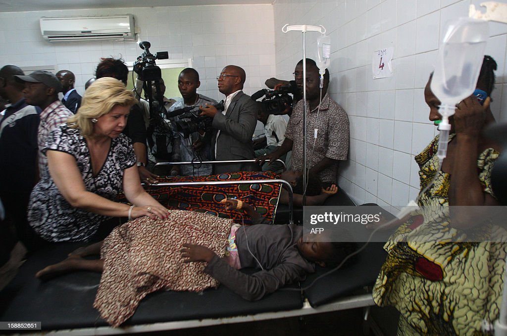 Dominique Ouattara (L), wife of President of The Ivory Coast Alassane Ouattara , stands next to a child, injured in a stampede, at the Cocody hospital in Abidjan, on January 1, 2013. At least 60 people died and at least dozens were injured as crowds stampeded overnight during celebratory New Year's fireworks, Ivory Coast rescue workers said on January 1, 2013. AFP PHOTO/HERVE SEVI