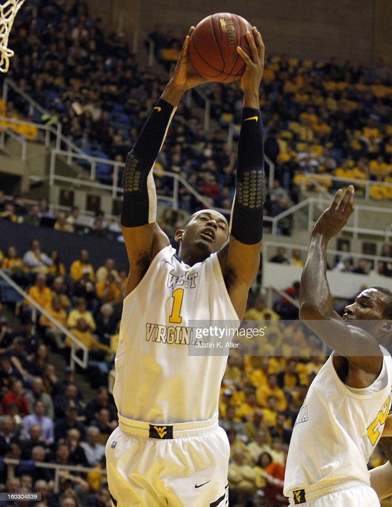 Dominique Rutledge #1 of the West Virginia Mountaineers pulls down a rebound against the Kansas Jayhawks at the WVU Coliseum on January 28, 2013 in Morgantown, West Virginia.