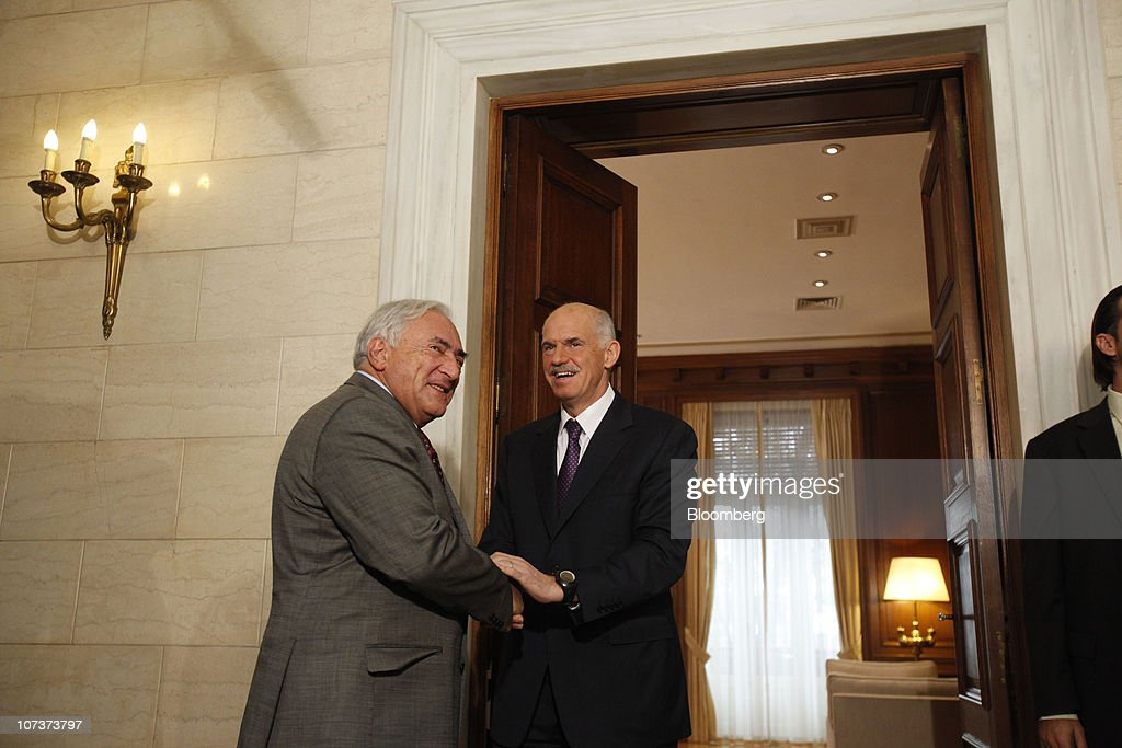Dominique StraussKahn managing director of the International Monetary Fund left is greeted by George Papandreou Greece's prime minister before talks...