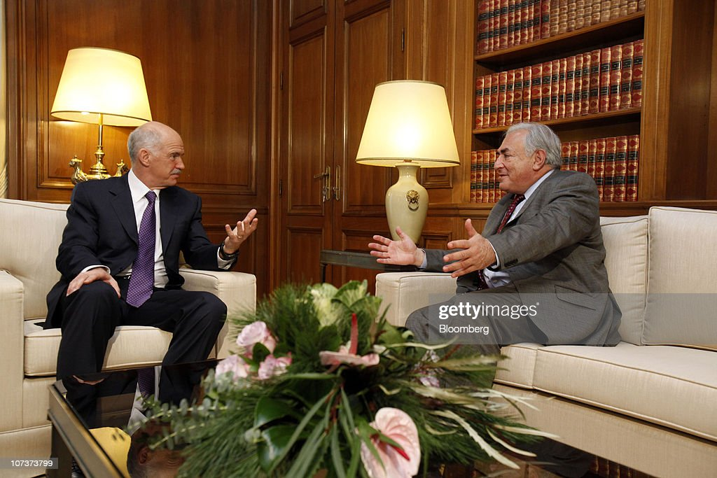 Dominique StraussKahn managing director of the International Monetary Fund right speaks with George Papandreou Greece's prime minister at Maximos...