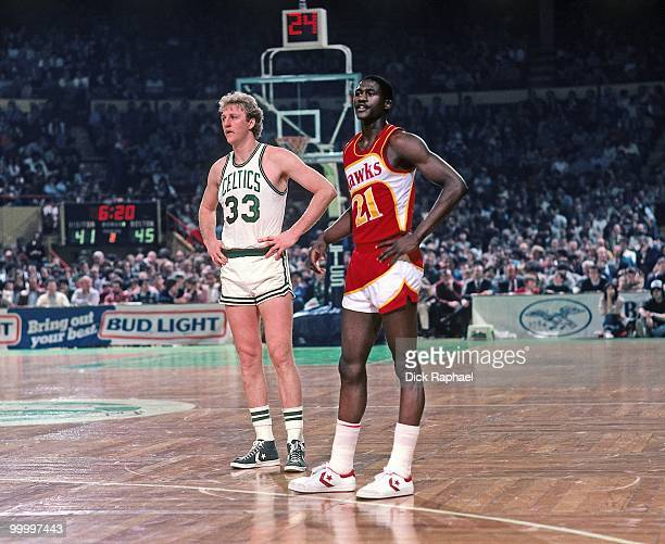 Dominique Wilkins of the Atlanta Hawks and Larry Bird of the Boston Celtics stand on the court during a game played in 1983 at the Boston Garden in...