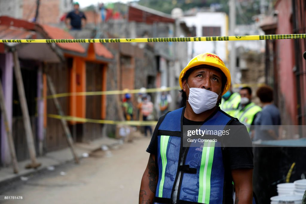 Domino Castillo watches search and rescue teams as they continue to search for victims trapped under the rubble at the Neto supermarket in the San Gregorio Atlapulco neighborhood of Delegacion Xochimilco on September 22, 2017 in Mexico City, Mexico. A powerful 7.1 earthquake rocked central Mexico on Tuesday, collapsing homes and bridges across hundreds of miles, killing at least 273 people.