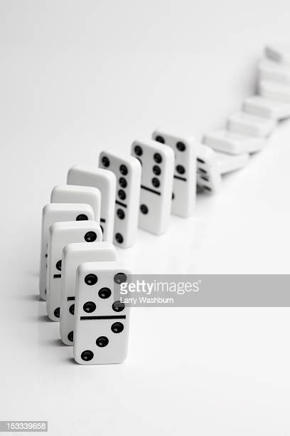 Dominoes falling over in a chain reaction