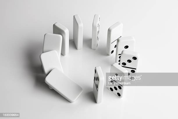 Dominoes in a circle beginning to fall over in a chain reaction