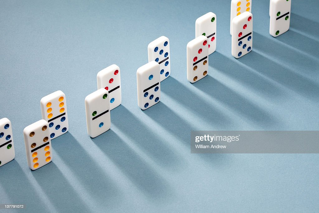 Dominoes lined up, casting shadow : Stock Photo