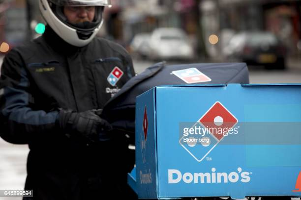 A Domino's Pizza logo sits on the delivery box of a courier outside a Domino's Pizza Group Plc store in Hanwell London UK on Monday Feb 27 2017...