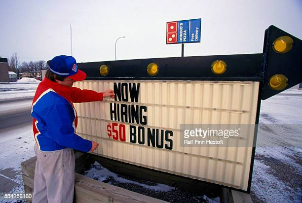 Domino's Pizza manager Roger Tangen posts an advertisement for a job with a $50 bonus for new workers at his store The sign reads 'NOW HIRING $50...