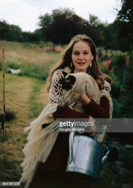Dominque Sanda Holding Cat and Water Can