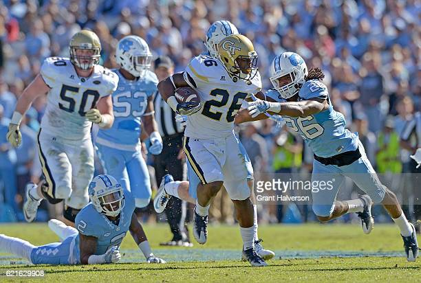 Dominquie Green of the North Carolina Tar Heels dives to tackle Dedrick Mills of the Georgia Tech Yellow Jackets during the game at Kenan Stadium on...