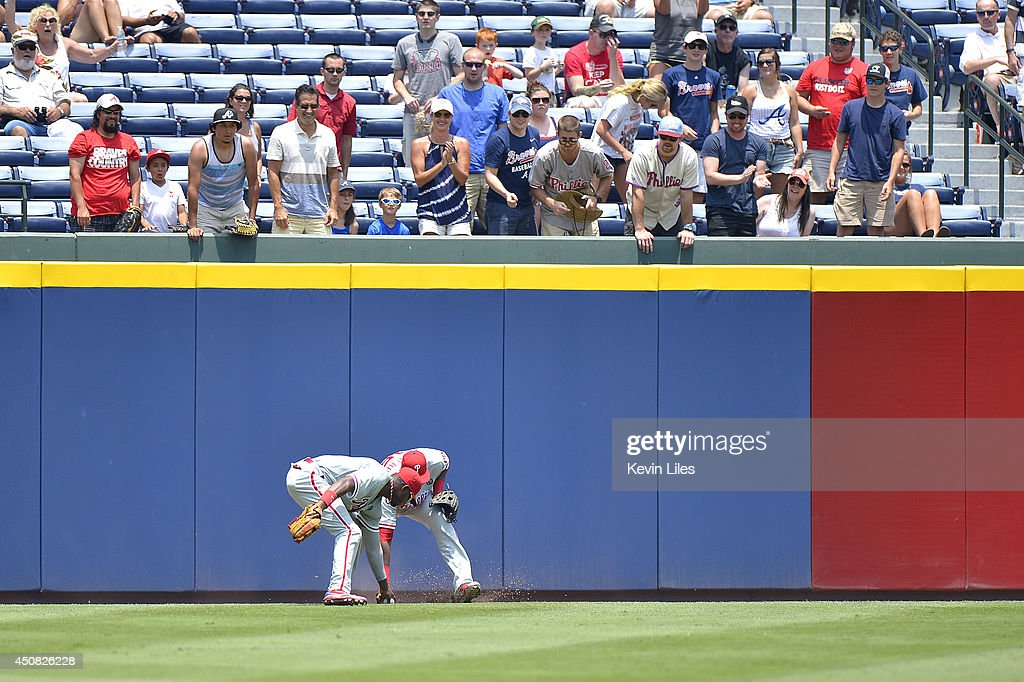 Domonic Brown (left) #9 of the Philadelphia Phillies and John Mayberry Jr. (right) #15 fields a ball during the fourth inning against the Atlanta Braves at Turner Field on June 18, 2014 in Atlanta, Georgia. The Braves won 10-5.