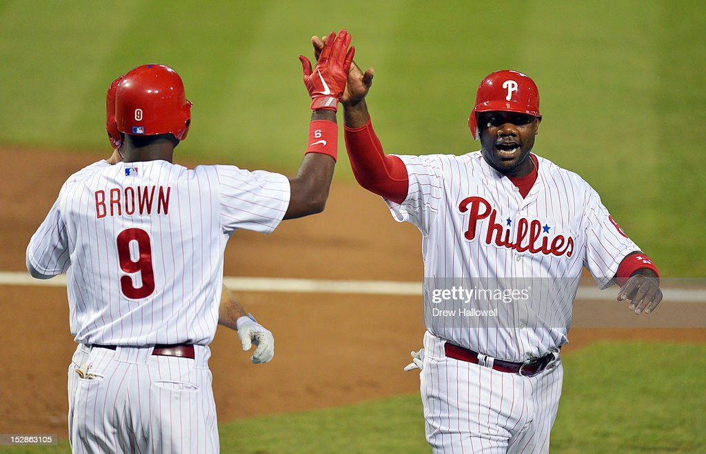 Domonic Brown #9 and Ryan Howard #6 of the Philadelphia Phillies celebrate scoring in the first inning on a double by Daron Ruf #18 (not pictured) against the Washington Nationals at Citizens Bank Park on September 27, 2012 in Philadelphia, Pennsylvania.