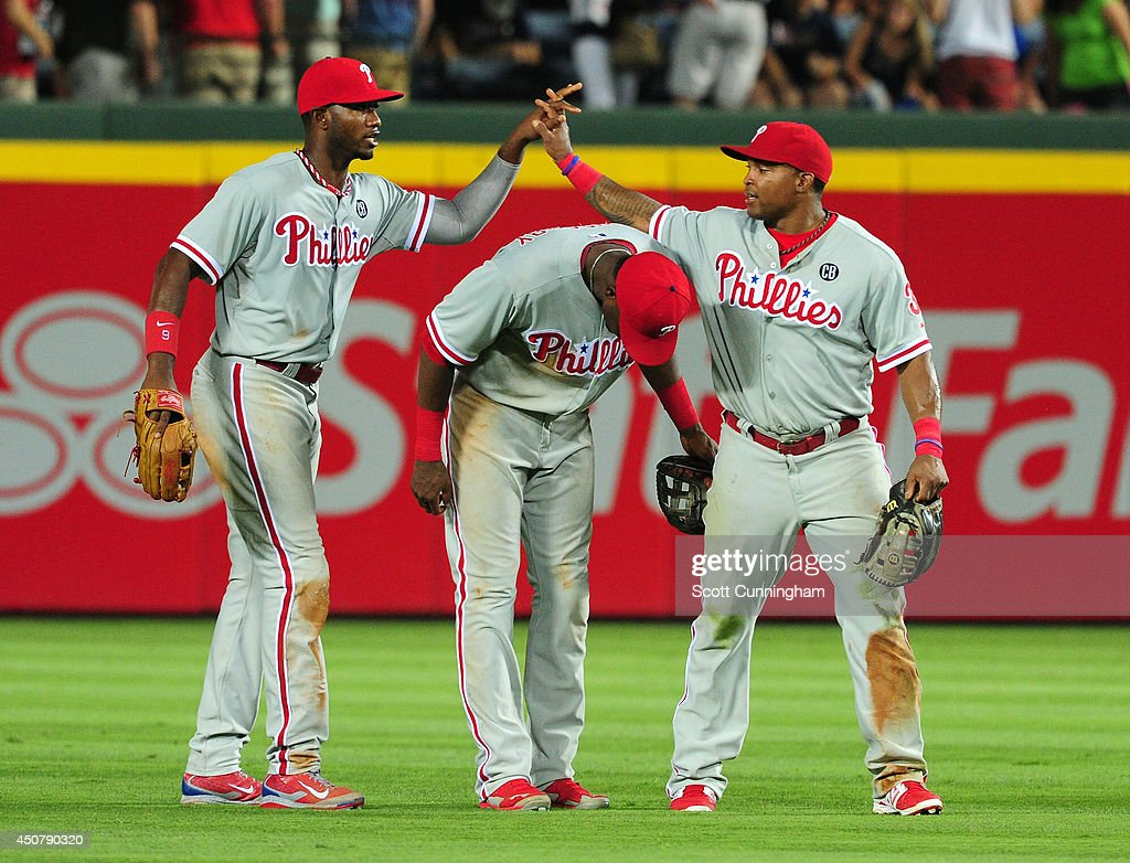 Domonic Brown #9, John Mayberry, Jr. #15, and Marlon Byrd #3 of the Philadelphia Phillies celebrate after defeating the Atlanta Braves at Turner Field on June 17, 2014 in Atlanta, Georgia.