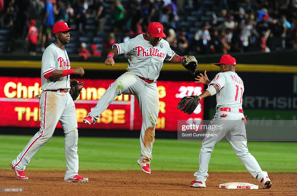 Domonic Brown #9, Marlon Byrd #3 and Jimmy Rollins #11 of the Philadelphia Phillies celebrate after defeating the Atlanta Braves at Turner Field on June 17, 2014 in Atlanta, Georgia.