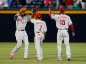 Domonic Brown Michael Martinez and John Mayberry Jr #15 of the Philadelphia Phillies celebrate after their 51 win in the ninth inning against the...