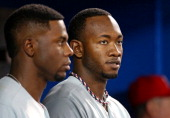 Domonic Brown of the Philadelphia Phillies and John Mayberry Jr #15 look on from the dugout during MLB game action against the Toronto Blue Jays on...