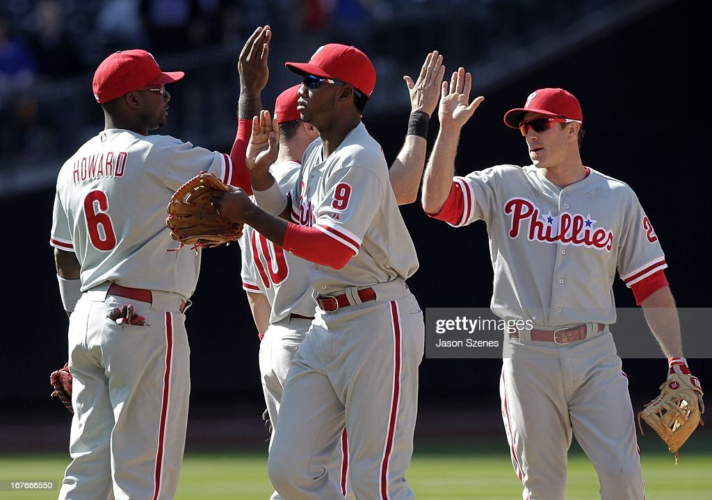Domonic Brown #9 of the Philadelphia Phillies (C) celebrates with his teammates <a gi-track='captionPersonalityLinkClicked' href=/galleries/search?phrase=Ryan+Howard&family=editorial&specificpeople=551402 ng-click='$event.stopPropagation()'>Ryan Howard</a> #6 (L) and <a gi-track='captionPersonalityLinkClicked' href=/galleries/search?phrase=Chase+Utley&family=editorial&specificpeople=161391 ng-click='$event.stopPropagation()'>Chase Utley</a> #26 (R) at the conclusion of the game against the New York Mets at Citi Field on April 27, 2013 in the Flushing neighborhood of the Queens borough of New York City. (Photo by Jason Szenes/Getty Images