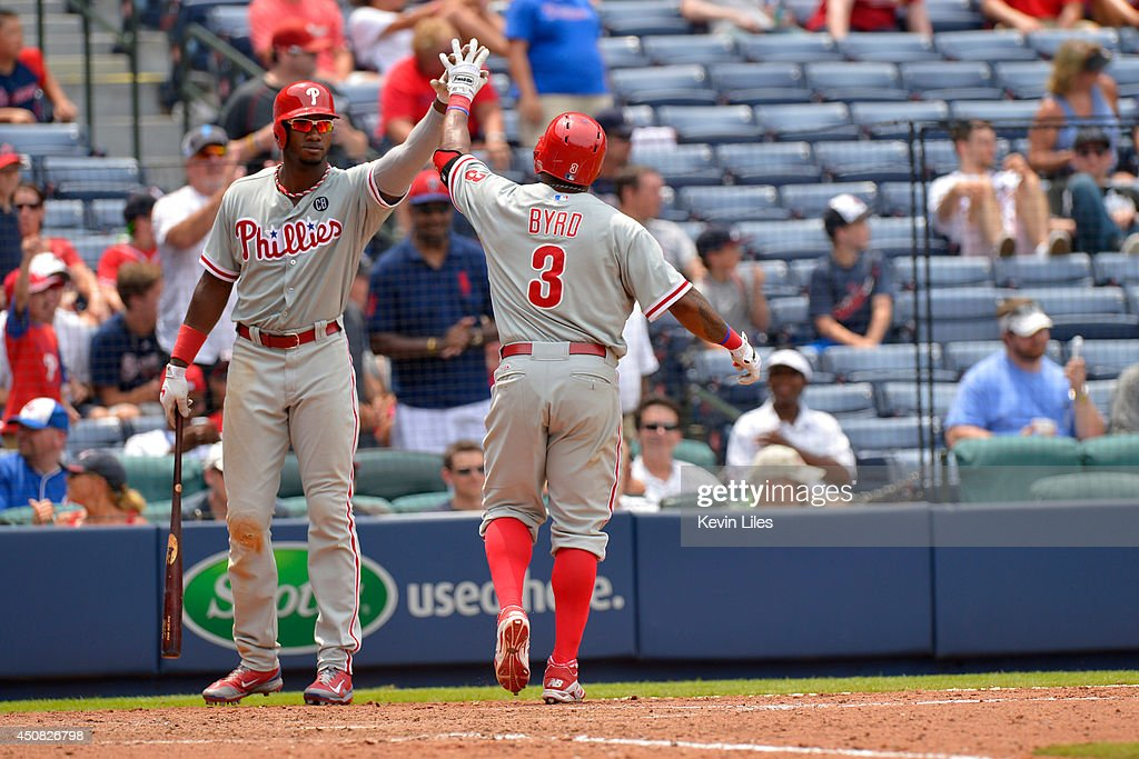 Domonic Brown #9 of the Philadelphia Phillies congratulates Marlon Byrd #3 after he hit a home run against the Atlanta Braves during the eighth inning at Turner Field on June 18, 2014 in Atlanta, Georgia.