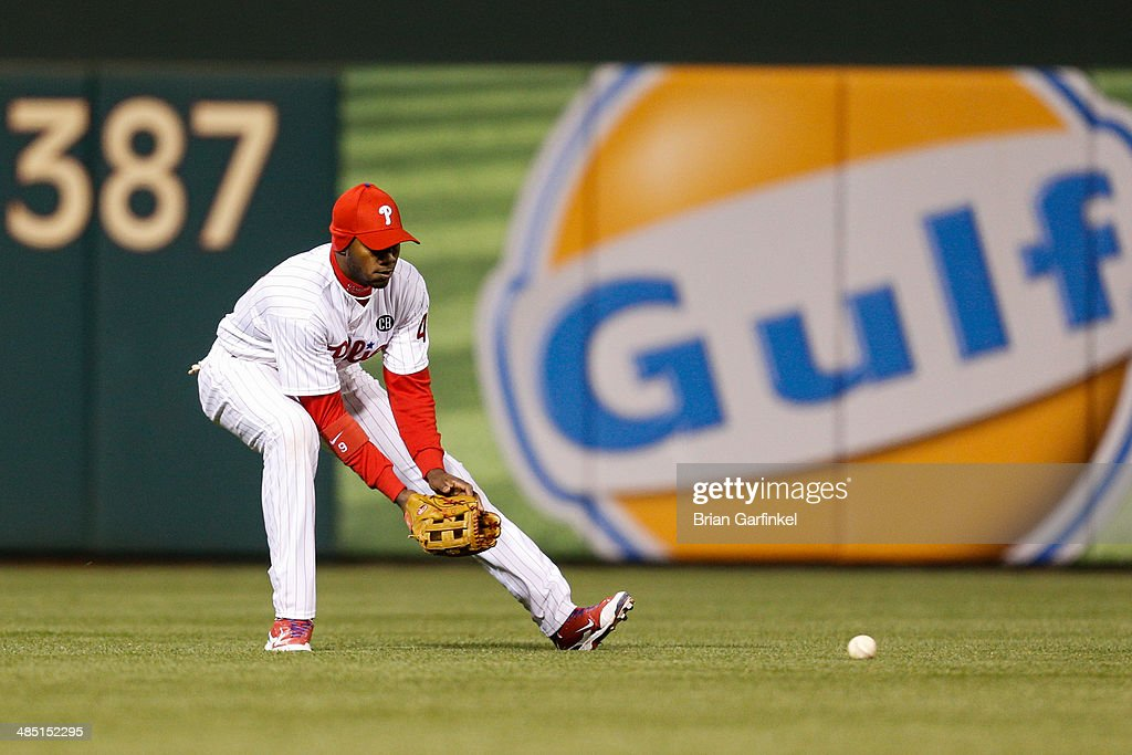 <a gi-track='captionPersonalityLinkClicked' href=/galleries/search?phrase=Domonic+Brown&family=editorial&specificpeople=6900643 ng-click='$event.stopPropagation()'>Domonic Brown</a> of the Philadelphia Phillies fields the ball int he ninth inning of the game against the Atlanta Braves at Citizens Bank Park on April 16, 2014 in Philadelphia, Pennsylvania. All uniformed team members are wearing jersey number 42 in honor of Jackie Robinson Day. The Braves won 1-0.