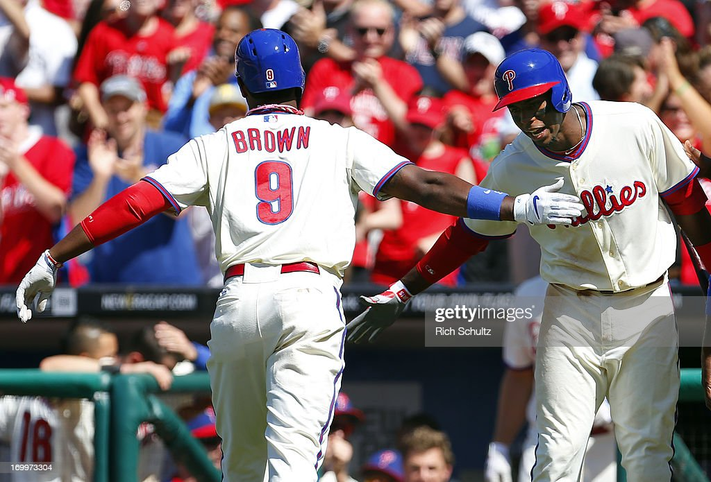 Domonic Brown #9 of the Philadelphia Phillies is congratulated by teammate John Mayberry #15 after hitting a two run home run in the seventh inning against the Miami Marlins on June 5, 2013 at Citizens Bank Park in Philadelphia, Pennsylvania. The Phillies defeated the Marlins 6-1.