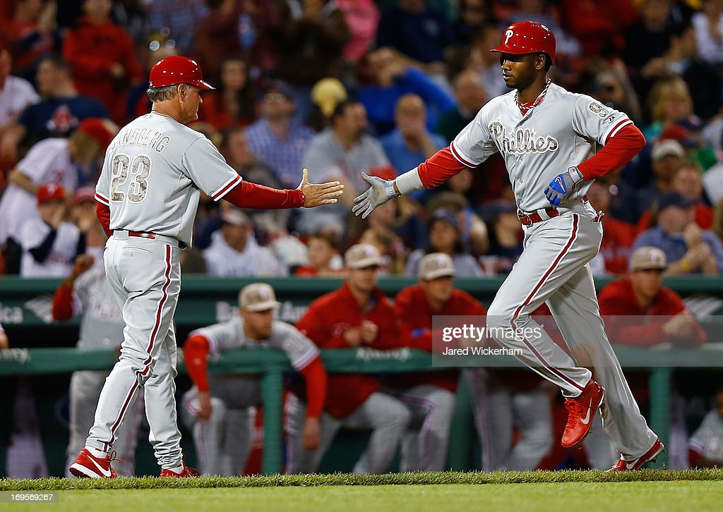 Domonic Brown #9 of the Philadelphia Phillies is congratulated by third base coach <a gi-track='captionPersonalityLinkClicked' href=/galleries/search?phrase=Ryne+Sandberg&family=editorial&specificpeople=206643 ng-click='$event.stopPropagation()'>Ryne Sandberg</a> #23 of the Philadelphia Phillies after hitting a two-run home run in the eighth inning against the Boston Red Sox during the interleague game on May 27, 2013 at Fenway Park in Boston, Massachusetts.