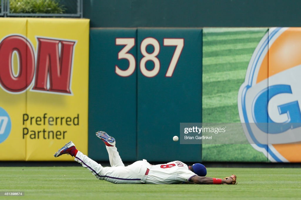 <a gi-track='captionPersonalityLinkClicked' href=/galleries/search?phrase=Domonic+Brown&family=editorial&specificpeople=6900643 ng-click='$event.stopPropagation()'>Domonic Brown</a> #9 of the Philadelphia Phillies is unable to catch a line drive hit by Chris Johnson #23 of the Atlanta Braves who doubled in the ninth inning of the first game of a doubleheader at Citizens Bank Park on June 28, 2014 in Philadelphia, Pennsylvania. The Braves won 10-3.