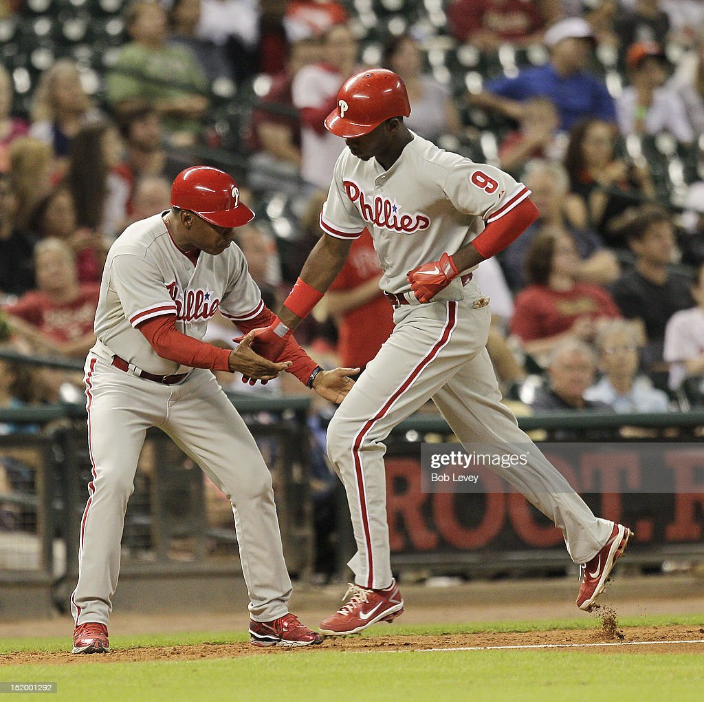 Domonic Brown #9 of the Philadelphia Phillies receives congratulations from Juan Samuel #12 after hitting a home run in the seventh inning against the Houston Astros at Minute Maid Park on September 14, 2012 in Houston, Texas.